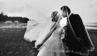 kissing newlyweds under a veil, black and white