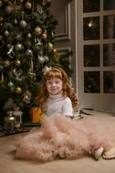 New Year's Eve, red haired child girl sits near christmas tree