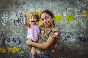 portrait of sisters on the grunge wall background