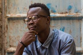 Portrait of Adult african man sitting at grunge wall