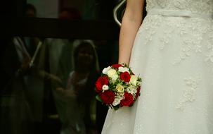a bouquet of roses in the hands of the bride