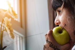 mature woman eating apple at window