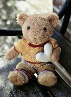 teddy bear with a white heart on a bench