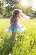 girl in a beautiful dress is dancing in the meadow