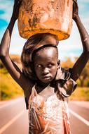 african child Girl standing on road with water in bucket on head
