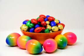 rainbow Colored Easter Eggs and bright chocolates in bowl