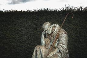 Statue of the shepherd man in loneliness on the cemetery