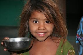 happy Child girl with metal bowl, india, Rajasthan