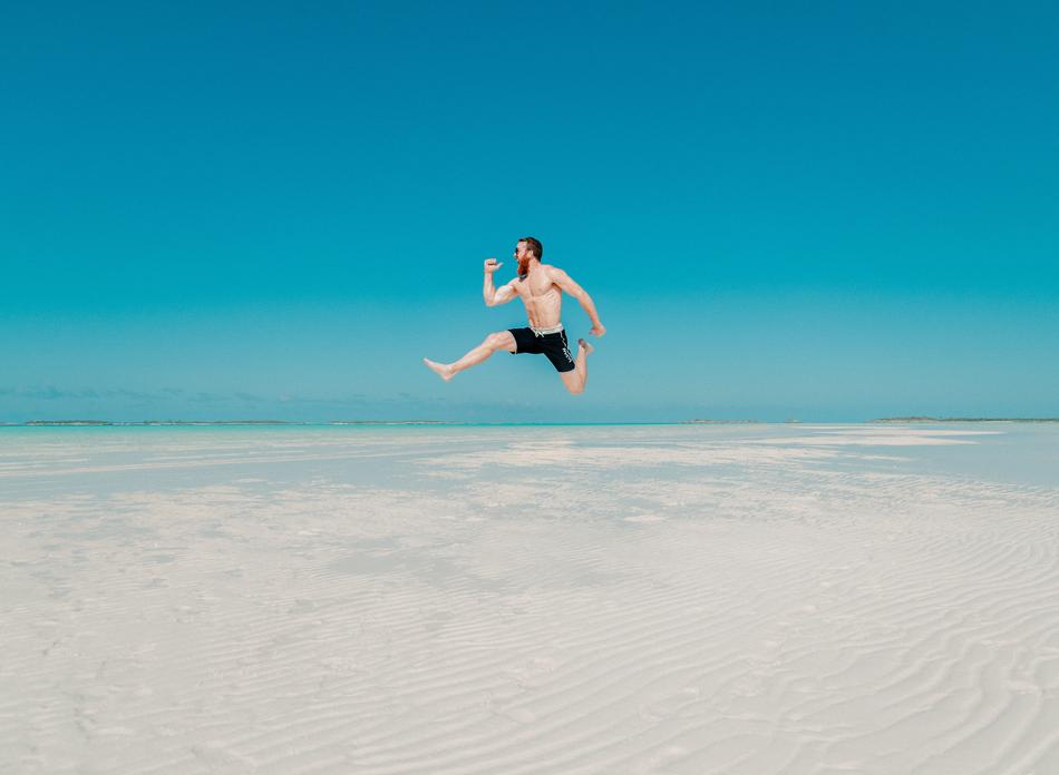 man is jumping on a tropical beach