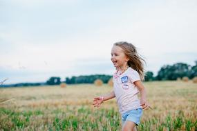 joyful girl runs on a flowering meadow