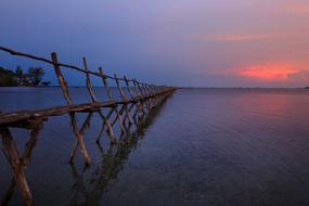 long weathered wooden pier in sea at tranquil sunset, Vietnam, Phu Quoc
