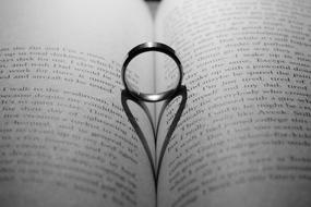 Love symbol, Ring with heart shape shadow on open book