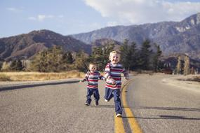 two little brothers are running down the highway
