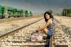 Woman with colorful suitcase sitting on a railway