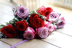 Beautiful bouquet of beautiful red and pink and white rose flowers on wooden surface