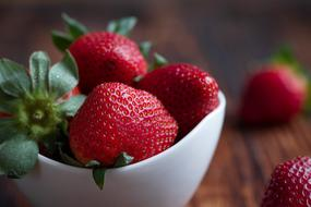 ripe strawberries in a white porcelain bowl