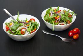 vegetable salad in two white bowls