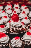 many cupcakes with cherries