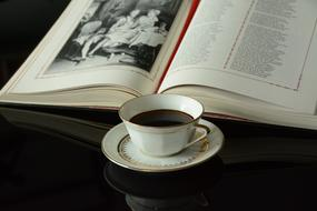 coffee in a porcelain cup and an open book