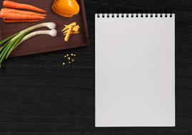 Writing Pad and raw Vegetables on Table