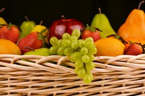 apples, pears, grapes and berries in a wicker basket