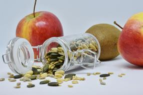 apples and sunflower and pumpkin seeds in a transparent jar
