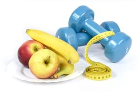 dumbbells, measuring tape and fruit on a plate