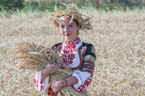 girl in national dress with a wheat crop in hands on a field in Burgas, Bulgaria
