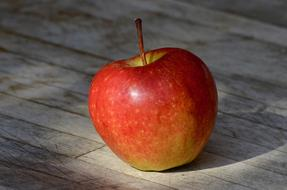 red ripe apple on a wooden table
