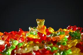 photo of multi-colored chewing bears on a black background