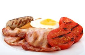 fried bacon, fried egg, grilled sausage and grilled tomatoes for breakfast