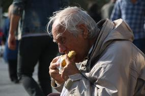 elderly man is eating boiled corn outdoors