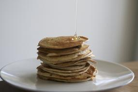 Honey pouring on top of stack of Pancakes