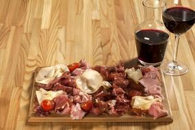 cold cuts on a board and a glass of red wine in a restaurant