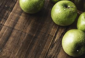 wet green apples on a wooden cutting board