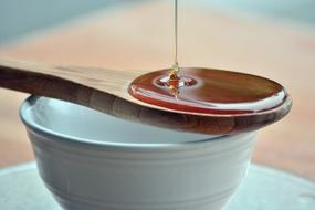 Honey pouring in wooden spoon on blue bowl