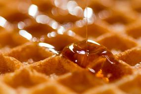 Syrup pouring on Belgian Waffle, macro