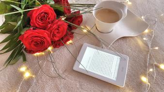 a bouquet of red roses a cup of coffee with milk and an e-book on the table