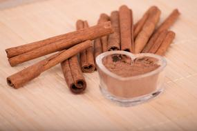 ground cinnamon in the shape of a heart and cinnamon sticks