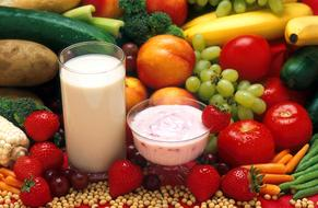 a glass of milk and yogurt on a background of ripe vegetables and fruits