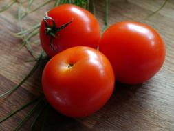 three red ripe tomatoes on a wooden surface close up