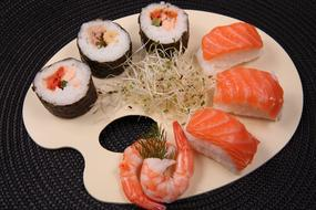 sushi and rolls on a wooden plate in a restaurant