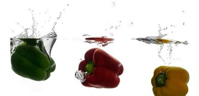 three colorful bell peppers drowning in water