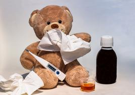 teddy bear with a thermometer and a scarf and medicine on the table