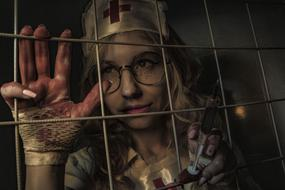 spooky nurse with Syringe behind grates