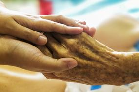 hold the elderly man's hand in a hospice