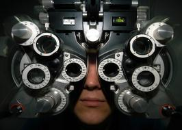Optometry equipment at person's eyes