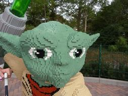 Beautiful, green, beige, red, black and white figure of Yoda, made of Lego blocks