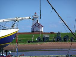 Beautiful landscape with the white and red lighthouse and ship on the Prince Edward Island in Canada