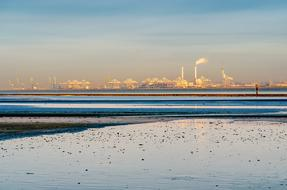 photo of a beach in Liman Bay against the background of an industrial plant